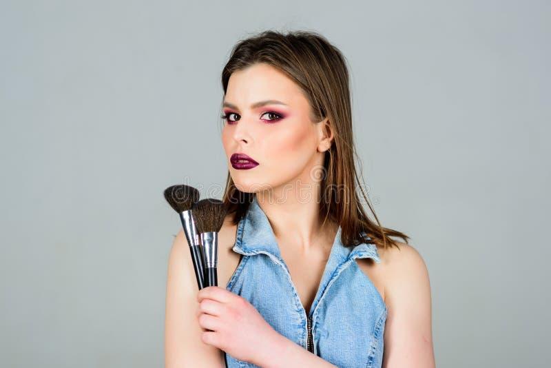 Να φανεί καλός και αίσθημα βέβαιος E Ελκυστική γυναίκα που εφαρμόζει makeup τη βούρτσα Επαγγελματικό makeup στοκ φωτογραφία