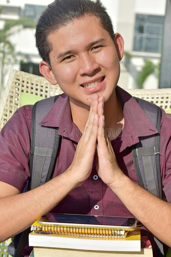 Νεανικός ασιατικός άνδρας σπουδαστής στην προσευχή στοκ εικόνα με δικαίωμα ελεύθερης χρήσης