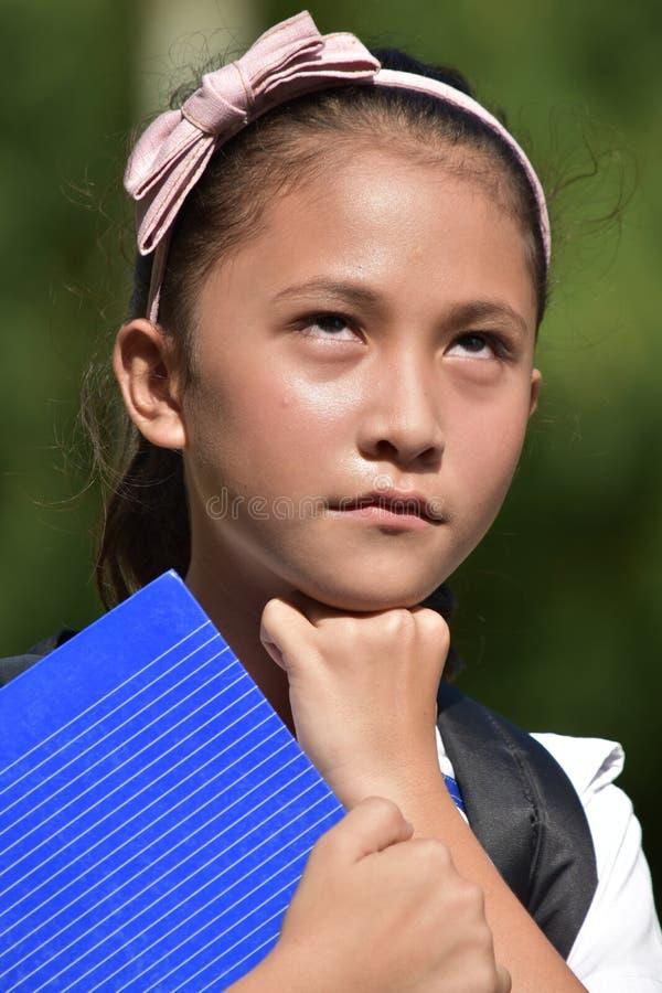 Νεανικός σπουδαστής κοριτσιών Filipina που σκέφτεται με τα σημειωματάρια στοκ φωτογραφία με δικαίωμα ελεύθερης χρήσης