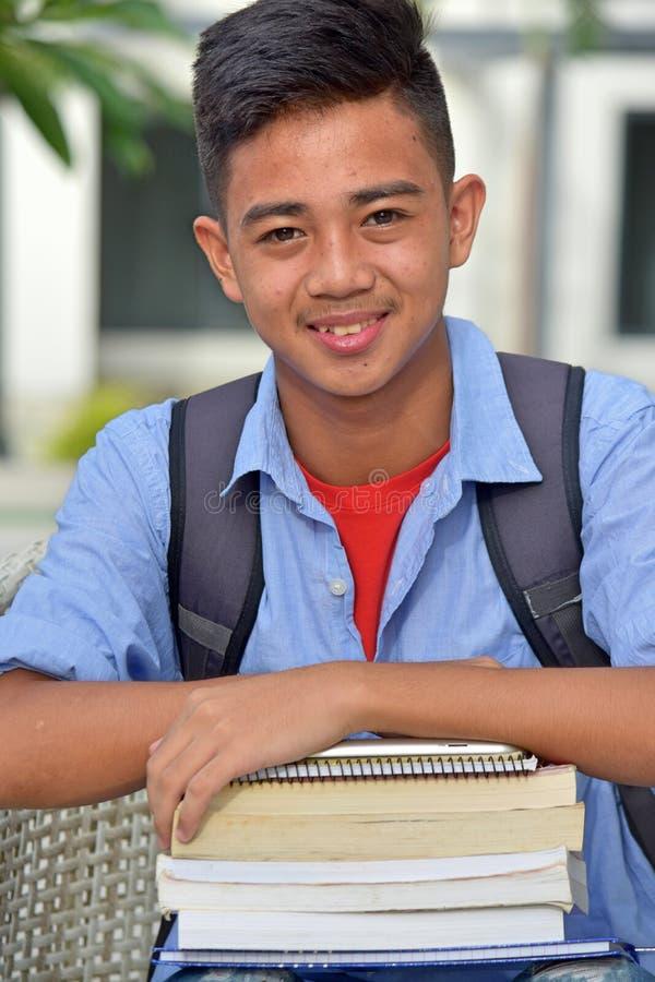 Νεανικός των Φηληππίνων σπουδαστής αγοριών που χαμογελά με τα σημειωματάρια στοκ φωτογραφίες με δικαίωμα ελεύθερης χρήσης