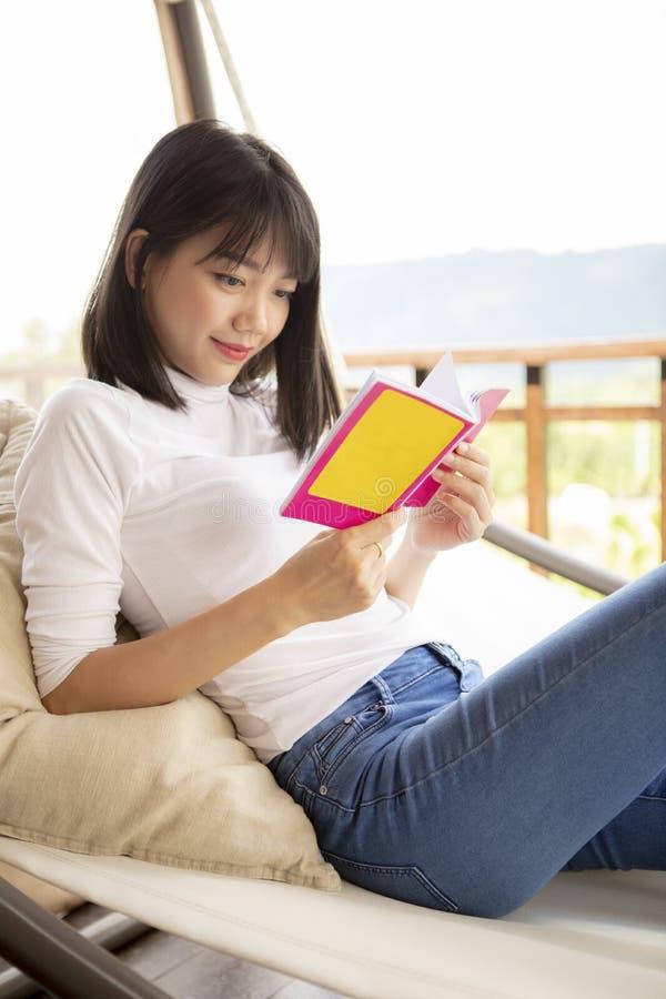 Νεαρά Ασιάτισσα που συσπειρώνει διαβάζοντας ένα βιβλίο στοκ φωτογραφίες