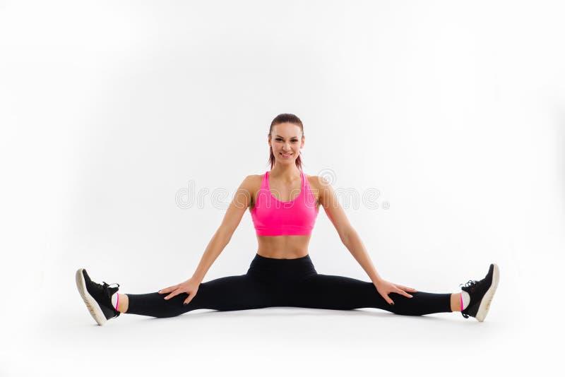 """Νεαρή αθλήτρια που κάθεται σε κομμάτια και τεντώνει Ï""""Î¿ σώμα της στοκ εικόνα με δικαίωμα ελεύθερης χρήσης"""
