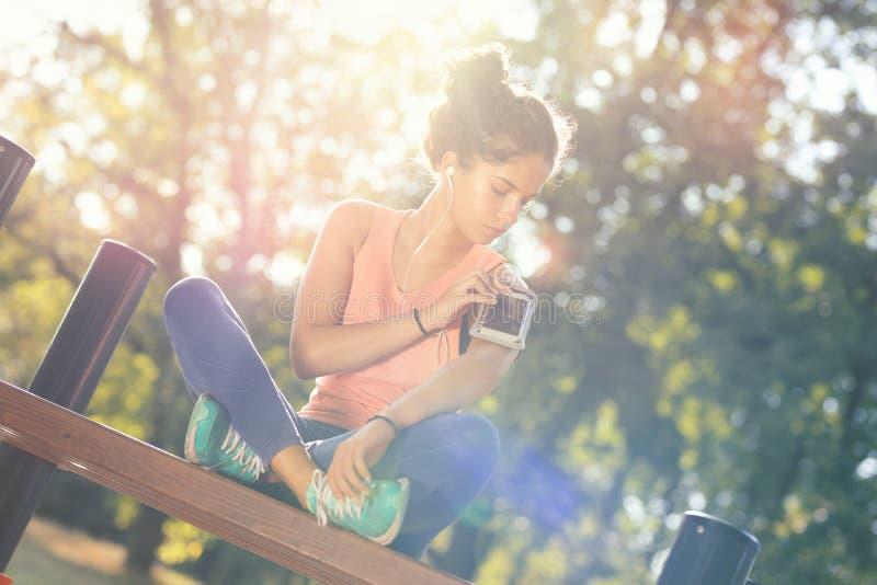 Νεαρή αθλήτρια χαλαρώνει με εξοπλισμό σε εξωτερικό γυμναστήριο στοκ εικόνες με δικαίωμα ελεύθερης χρήσης