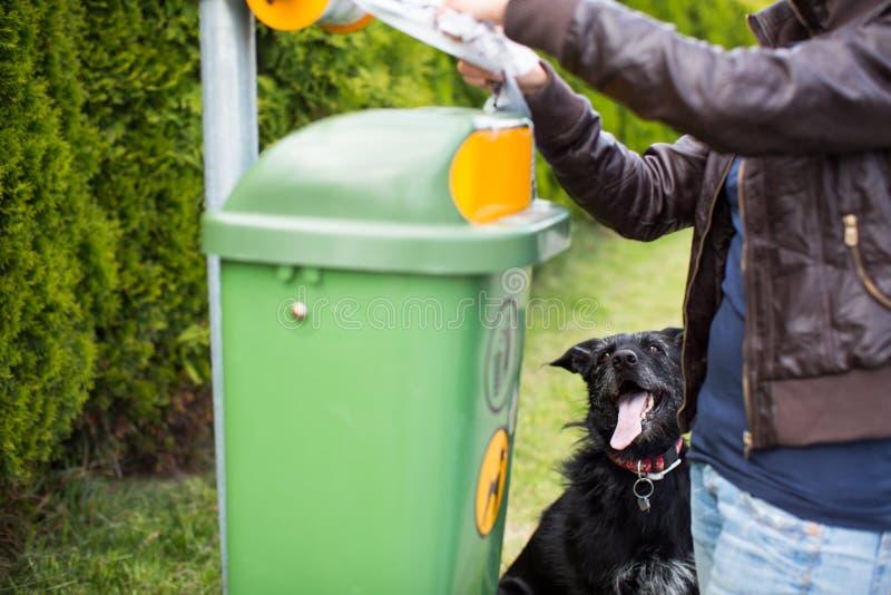Νεαρή γυναίκα αρπάζει μια πλαστική σακούλα σε ένα πάρκο για να τακτοποΠστοκ φωτογραφία με δικαίωμα ελεύθερης χρήσης