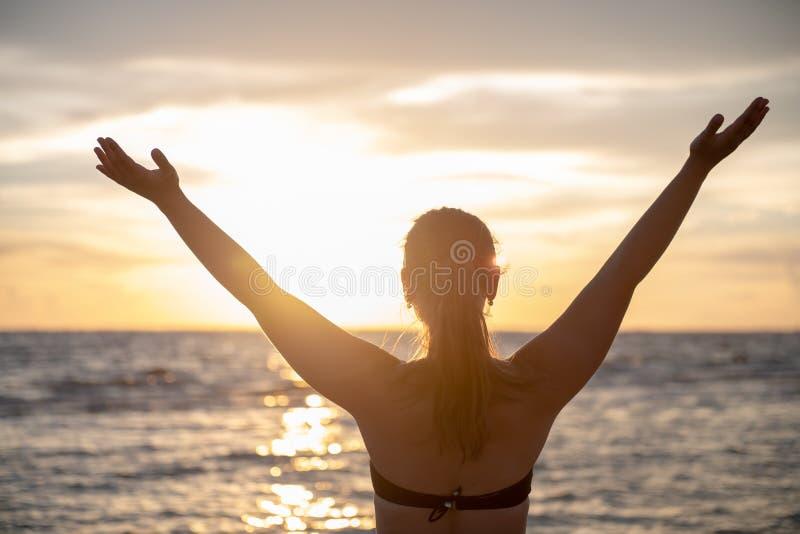 Νεαρή γυναίκα και ηλιοβασίλεμα στην παραλία στοκ εικόνες