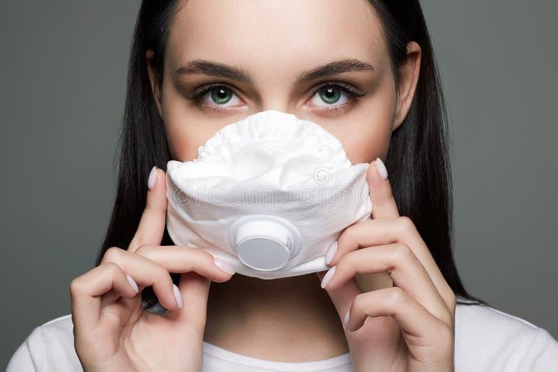 Νεαρή γυναίκα με μάσκα ιατρικό μασκοφόρο όμορφο κορίτσι στοκ εικόνα