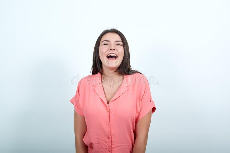 Νεαρή γυναίκα πάνω από λευκό τοίχο φωνάζει μπροστά με ανοιχτό το στόμα στοκ φωτογραφία