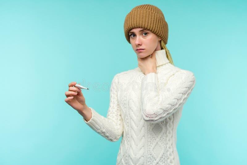Νεαρή γυναίκα που έχει φτάσει να παίρνει θερμόμετρο σε μπλε φόντο Η όμορφη κυρία είναι άρρωστη με υψηλή θερμοκρασία και πονόλαιμο στοκ φωτογραφίες