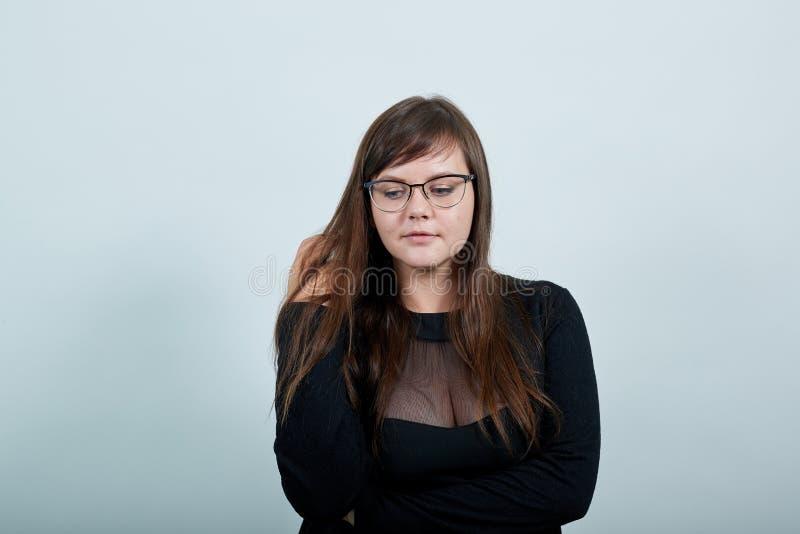 Νεαρή γυναίκα που κοιτάζει κάτω, κρατώντας το χέρι στα μαλλιά, έχοντας περιστασιακά γυαλιά στοκ εικόνες με δικαίωμα ελεύθερης χρήσης