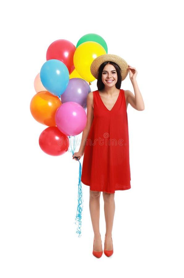 Νεαρή γυναίκα που κρατά ένα σωρό πολύχρωμα μπαλόνια στοκ εικόνα με δικαίωμα ελεύθερης χρήσης