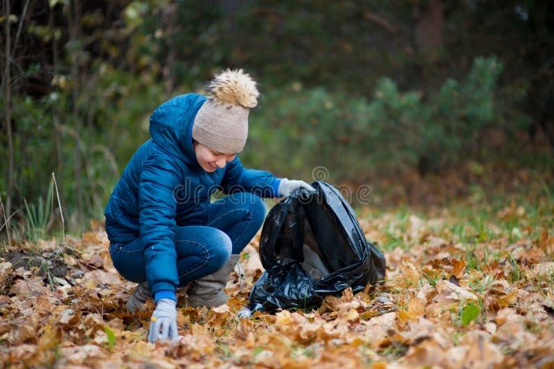 Νεαρή γυναίκα συλλέγει σκουπίδια σε μια τσάντα στο φθινοπωρινό δάσος στοκ εικόνες με δικαίωμα ελεύθερης χρήσης