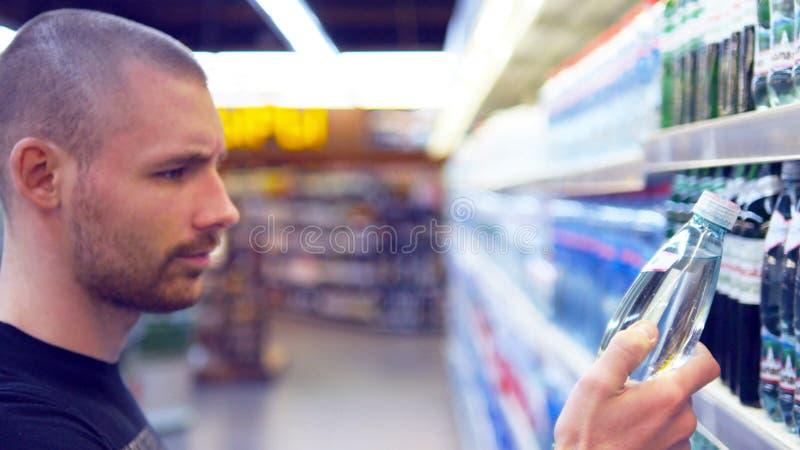 Νεαρή επιλογή άνδρων και μπουκάλι αγοράς του μεταλλικού νερού στην υπεραγορά Τύπος που παίρνει το προϊόν από τα ράφια στο παντοπω στοκ φωτογραφία με δικαίωμα ελεύθερης χρήσης
