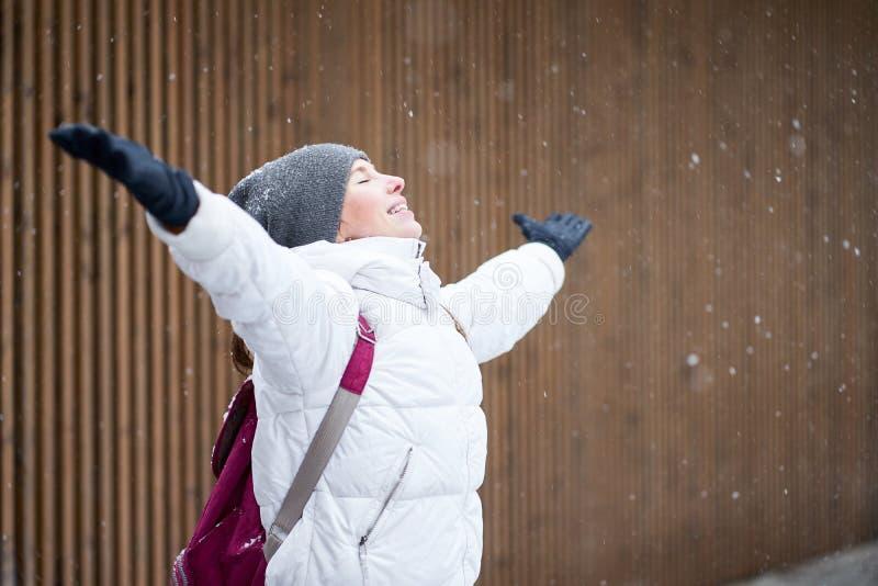 Νεαρή χαμογελαστή καυκάσα ντυμένη με λευκό σακάκι που απολαμβάνει το πρώτο χιόνι με κλειστά μάτια και σηκωμένα χέρια στοκ φωτογραφία με δικαίωμα ελεύθερης χρήσης
