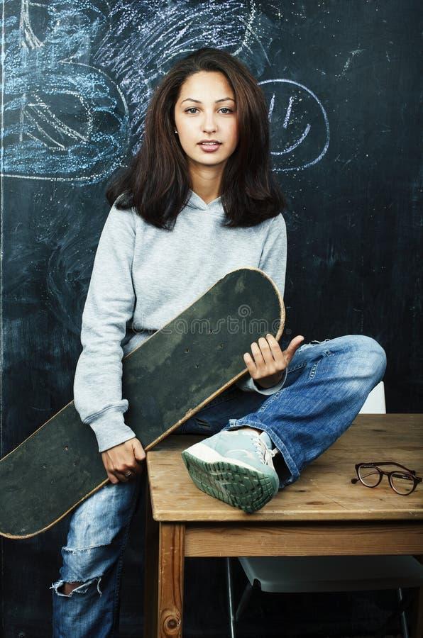 Νεαρή χαριτωμένη έφηβη σε τάξη σε μαύρη σανίδα καθισμένη στο τραπέζι χαμογελαστή, μοντέρνα χίπστερ ιδέα στοκ φωτογραφίες με δικαίωμα ελεύθερης χρήσης