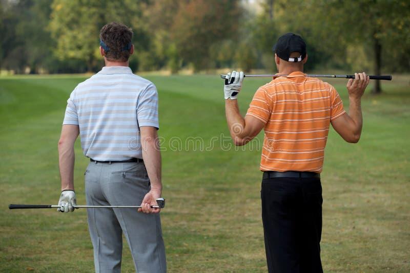 Νεαροί άνδρες που στέκονται στο γήπεδο του γκολφ με τα ραβδιά, οπισθοσκόπα στοκ φωτογραφία