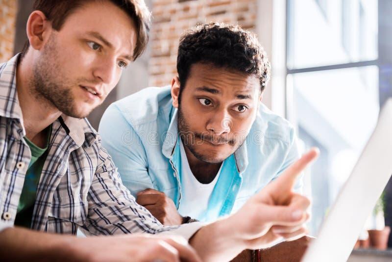 Νεαροί άνδρες που χρησιμοποιούν το lap-top μαζί στο σπίτι, νέα επαγγελματική έννοια ομάδας στοκ εικόνα