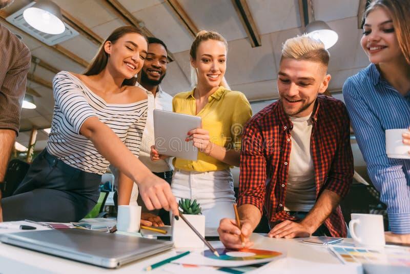 Νεαροί σχεδιαστές που συζητούν ιδέες για σχέδια και επιλέγουν χρώματα στοκ εικόνες με δικαίωμα ελεύθερης χρήσης