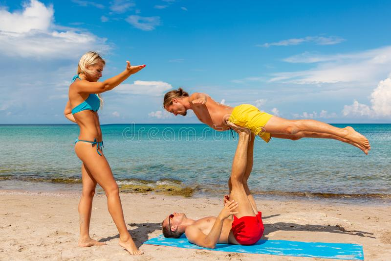 Νεαρός άνδρας δύο και γυναίκα στην παραλία που κάνει την άσκηση γιόγκας ικανότητας από κοινού Στοιχείο Acroyoga για τη δύναμη και στοκ φωτογραφία με δικαίωμα ελεύθερης χρήσης