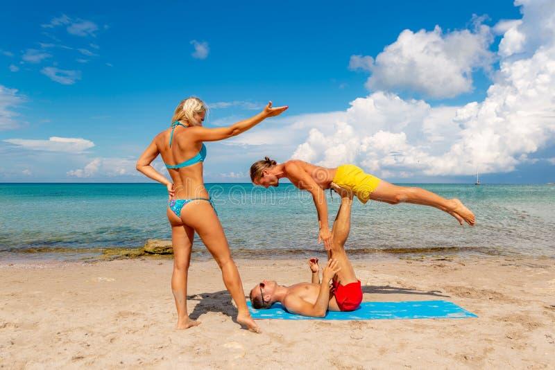 Νεαρός άνδρας δύο και γυναίκα στην παραλία που κάνει την άσκηση γιόγκας ικανότητας από κοινού Στοιχείο Acroyoga για τη δύναμη και στοκ φωτογραφίες με δικαίωμα ελεύθερης χρήσης