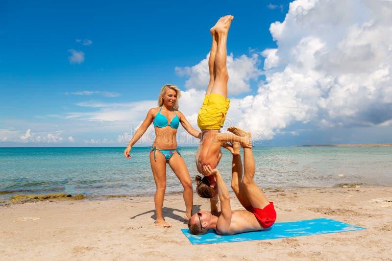 Νεαρός άνδρας δύο και γυναίκα στην παραλία που κάνει την άσκηση γιόγκας ικανότητας από κοινού Στοιχείο Acroyoga για τη δύναμη και στοκ εικόνες με δικαίωμα ελεύθερης χρήσης