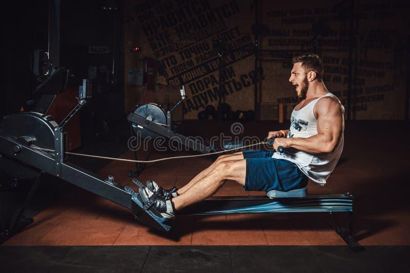 Νεαρός άνδρας ικανότητας που χρησιμοποιεί τη μηχανή κωπηλασίας στη γυμναστική και κραυγή στοκ φωτογραφία με δικαίωμα ελεύθερης χρήσης