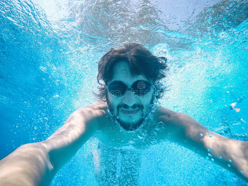 Νεαρός άνδρας κάτω από το νερό μιας πισίνας στοκ φωτογραφία με δικαίωμα ελεύθερης χρήσης