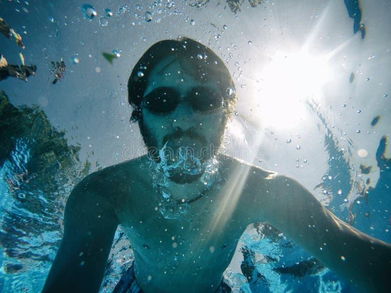 Νεαρός άνδρας κάτω από το νερό μιας πισίνας στοκ φωτογραφίες
