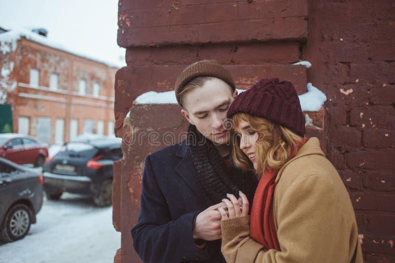 Νεαρός άνδρας και γυναίκα που αγκαλιάζουν κοντά στη γωνία τούβλου της οικοδόμησης Χειμερινή οδός Μυστικότητα στις απομονωμένες θέ στοκ φωτογραφία