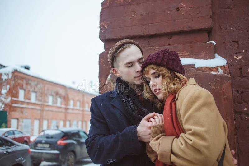 Νεαρός άνδρας και γυναίκα που αγκαλιάζουν κοντά στη γωνία τούβλου της οικοδόμησης Χειμερινή οδός Μυστικότητα στις απομονωμένες θέ στοκ φωτογραφίες