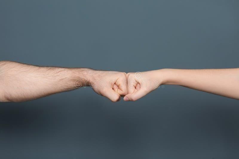 Νεαρός άνδρας και γυναίκα που κάνουν την πρόσκρουση πυγμών στοκ φωτογραφίες