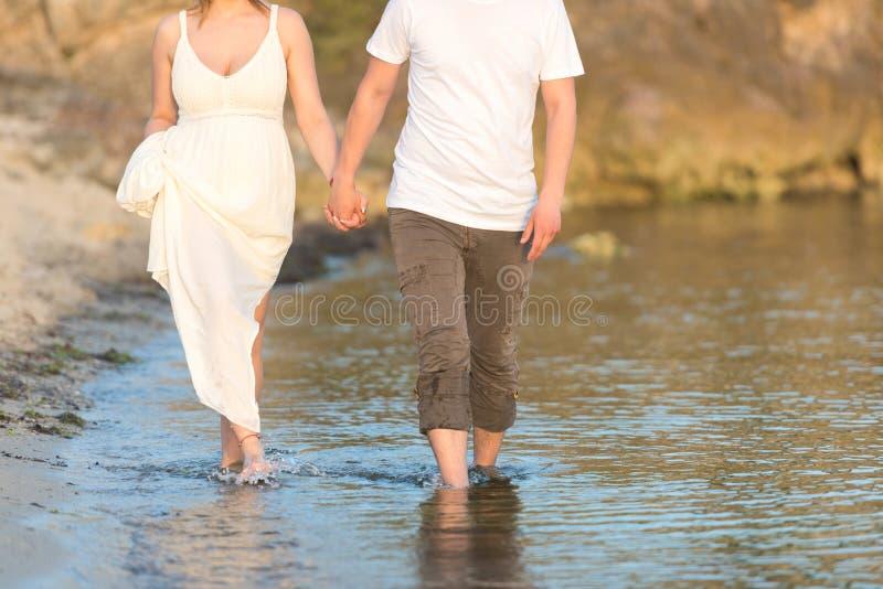 Νεαρός άνδρας και γυναίκα που περπατούν στην παραλία μαζί στο ηλιοβασίλεμα, κινηματογράφηση σε πρώτο πλάνο σωμάτων στοκ φωτογραφία με δικαίωμα ελεύθερης χρήσης