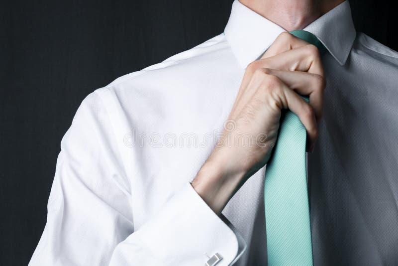 Νεαρός άνδρας κινηματογραφήσεων σε πρώτο πλάνο σε ένα άσπρο πουκάμισο με μια μέντα χρώματος δεσμών στοκ φωτογραφία