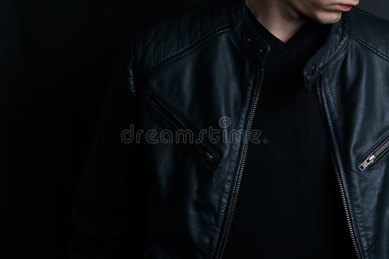 Νεαρός άνδρας κινηματογραφήσεων σε πρώτο πλάνο σε ένα μαύρο σακάκι δέρματος στοκ εικόνες