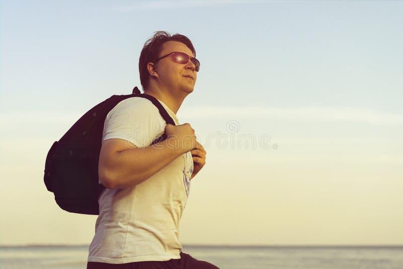 Νεαρός άνδρας με ένα σακίδιο πλάτης στους ώμους και τα γυαλιά ηλίου του που εξετάζουν το ηλιοβασίλεμα στο υπόβαθρο θάλασσας Ελευθ στοκ εικόνες με δικαίωμα ελεύθερης χρήσης
