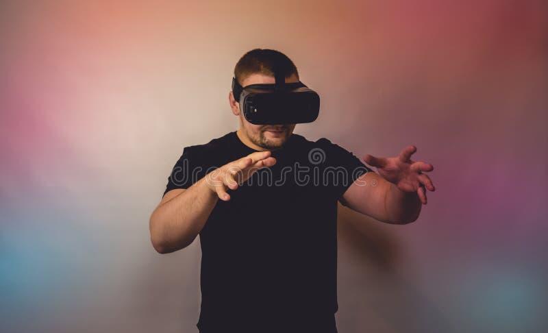 Νεαρός άνδρας με τα γυαλιά εικονικής πραγματικότητας o Η εικόνα περιέχει τον υπερβολικό θόρυβο, σιτάρι ταινιών, χειροποίητα αντικ στοκ εικόνες