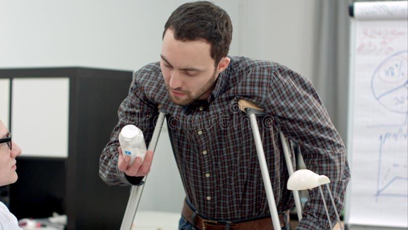 Νεαρός άνδρας με τα δεκανίκια που εξετάζει τα χάπια που ορίζονται από το γιατρό στοκ εικόνες