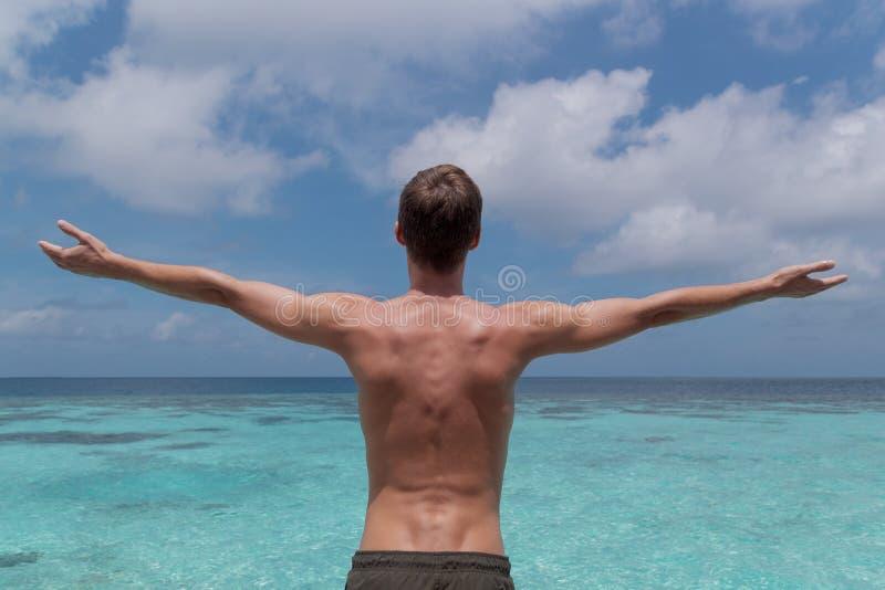 Νεαρός άνδρας με τα όπλα που αυξάνονται μπροστά από το σαφές μπλε νερό σε έναν τροπικό προορισμό διακοπών στοκ φωτογραφίες