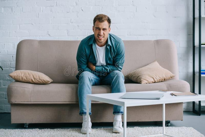 νεαρός άνδρας με την κοιλιακή συνεδρίαση πόνου στον καναπέ και το κοίταγμα στοκ εικόνα