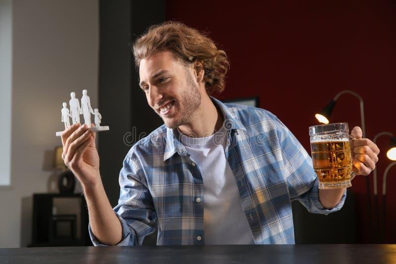 Νεαρός άνδρας με την κούπα της μπύρας και του αριθμού στον πίνακα Έννοια της επιλογής μεταξύ του οινοπνεύματος και της οικογένεια στοκ φωτογραφία με δικαίωμα ελεύθερης χρήσης