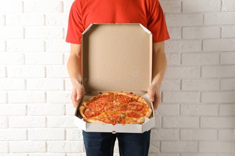Νεαρός άνδρας με το ανοιγμένο κιβώτιο πιτσών κοντά στον άσπρο τοίχο Υπηρεσία παράδοσης τροφίμων στοκ φωτογραφία