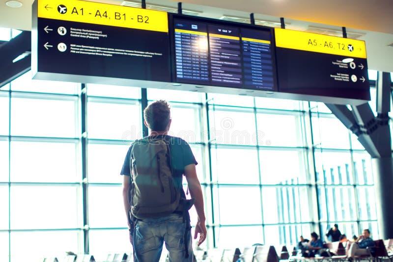 Νεαρός άνδρας με το σακίδιο πλάτης στον αερολιμένα κοντά στο χρονοδιάγραμμα πτήσης Ταξίδι στοκ εικόνα με δικαίωμα ελεύθερης χρήσης