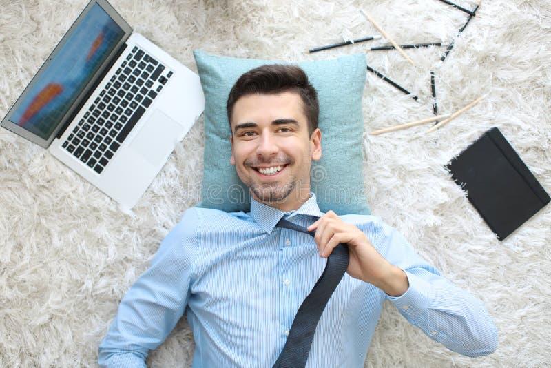 Νεαρός άνδρας με το lap-top που βγάζει το δεσμό στον τάπητα, στοκ φωτογραφίες