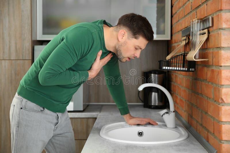 Νεαρός άνδρας που έχει τη ναυτία στην κουζίνα στοκ εικόνες