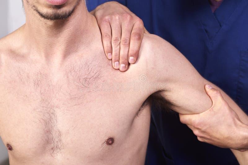 Νεαρός άνδρας που έχει chiropractic τη ρύθμιση ώμων Φυσιοθεραπεία, αποκατάσταση αθλητικών τραυματισμών Οστεοπάθεια, εναλλακτική ι στοκ φωτογραφία