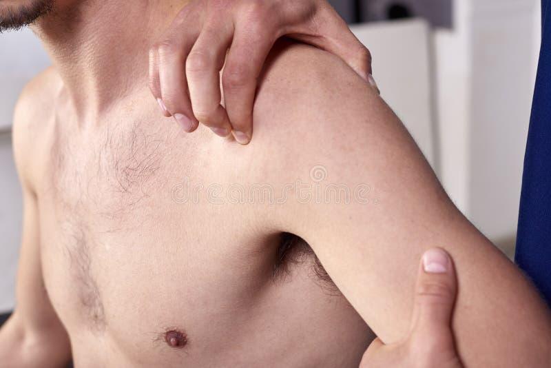 Νεαρός άνδρας που έχει chiropractic τη ρύθμιση ώμων Φυσιοθεραπεία, αποκατάσταση αθλητικών τραυματισμών Οστεοπάθεια, εναλλακτική ι στοκ εικόνα