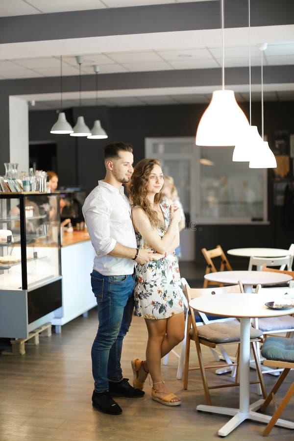 Νεαρός άνδρας που αγκαλιάζει το κορίτσι και που στέκεται στον καφέ κοντά στους πίνακες στοκ εικόνες