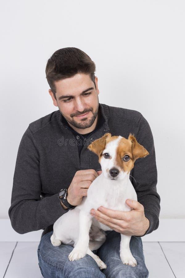 Νεαρός άνδρας που αγκαλιάζει το μικρό άσπρο σκυλί E αγάπη για την έννοια κατοικίδιων ζώων indoors lifestyle στοκ φωτογραφία