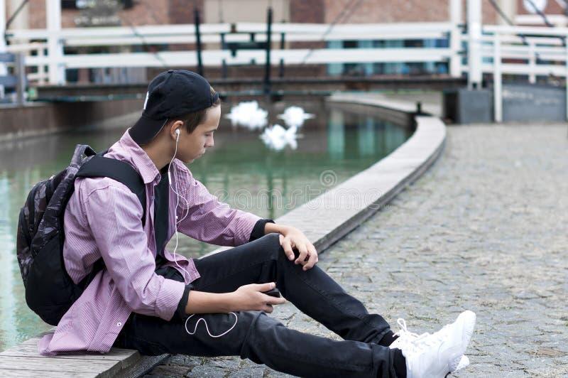 Νεαρός άνδρας που ακούει τη συνεδρίαση μουσικής στο πεζοδρόμιο στοκ φωτογραφία με δικαίωμα ελεύθερης χρήσης