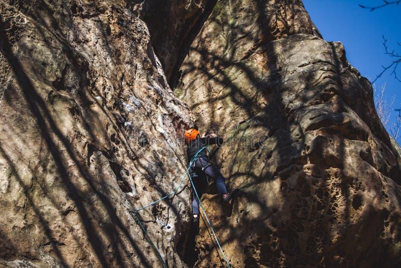 Νεαρός άνδρας που αναρριχείται στον απότομο βράχο ψαμμίτη στο δάσος στοκ εικόνα με δικαίωμα ελεύθερης χρήσης