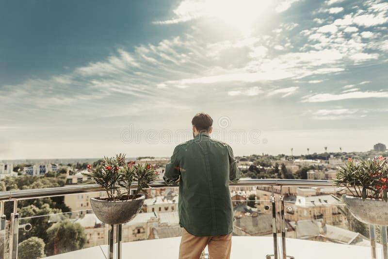 Νεαρός άνδρας που απολαμβάνει τη θέα από το μπαλκόνι στοκ εικόνες